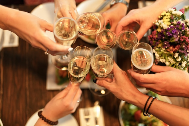 Девичник. девочки приветствуют бокалы с шампанским в ресторане. Premium Фотографии