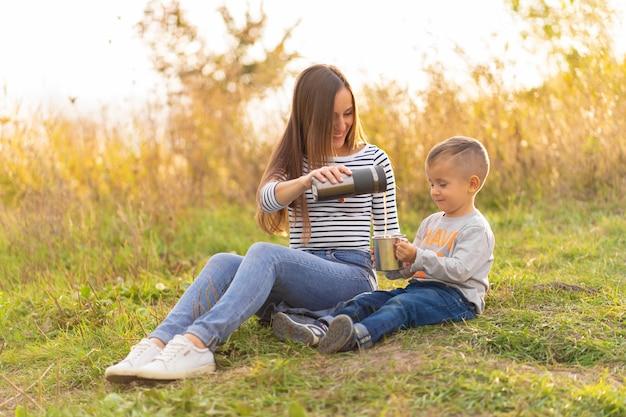 秋の散歩に幸せな家族。小さな息子を持つ若い美しい母親は、自然を楽しみます。 Premium写真