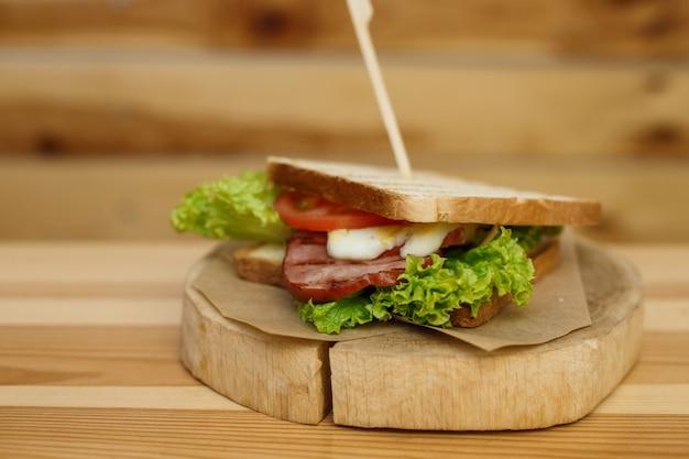 焼きパンとベーコンのジューシーなサンドイッチは、木製のプレートであなたを待っています Premium写真