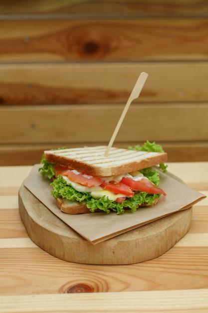 ジューシーなサンドイッチ、ベーコン、新鮮な野菜、グリーンサラダ、木製プレートのグリル後の暗い線 Premium写真