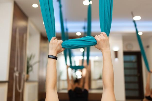 ジムでストレッチ体操を行うフライヨガをやっている女性 Premium写真