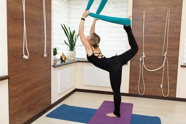 Женщина делает муху йоги, растяжения стоя на одной ноге на земле и второй в гамаке Premium Фотографии