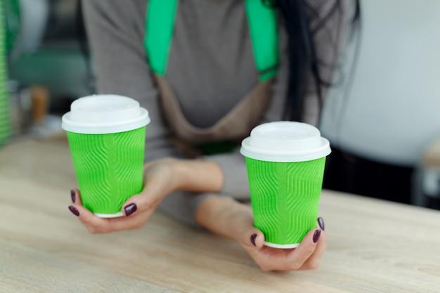 エプロンのバリスタは、緑の持ち帰り用の紙コップでホットコーヒーを手に持っています。 Premium写真