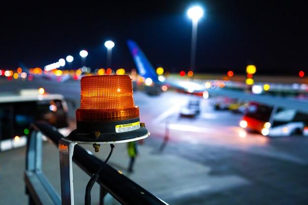 大型空港設備に注目を集める夜の写真、クローズアップ、黄色のビーコン。ぼやけた航空機の駐車場 Premium写真