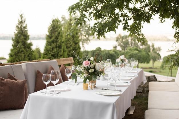 真ちゅう製の花瓶に生花で飾られた結婚式のテーブルセッティング Premium写真