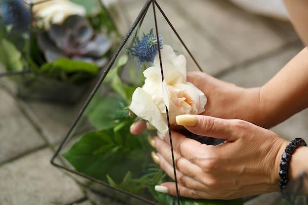 女性の花屋は、新鮮な多肉植物とバラの花をガラスの植物園に入れます。 Premium写真