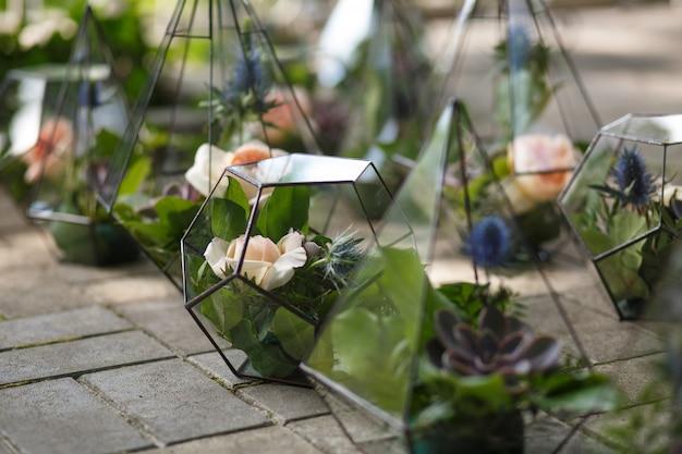 新鮮な多肉植物とバラの花を持つフロラリウム。 Premium写真