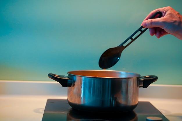 Приготовление супа на сковороде на индукционной плите Premium Фотографии