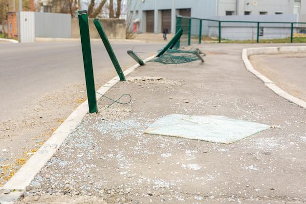 路上の事故の場所。曲がった柱と道路上の壊れた車のガラス Premium写真