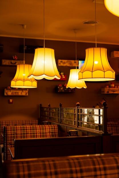 カフェの居心地の良いインテリア。暖かい黄色のライトシャンデリアと市松模様のソファ Premium写真