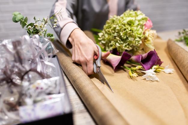 Флорист режет упаковочную бумагу для букета цветов. Premium Фотографии