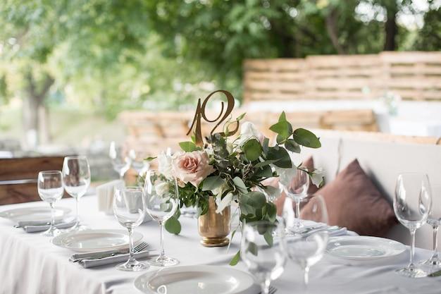 真ちゅう製の花瓶に生花で飾られた結婚式のテーブルセッティング。 Premium写真
