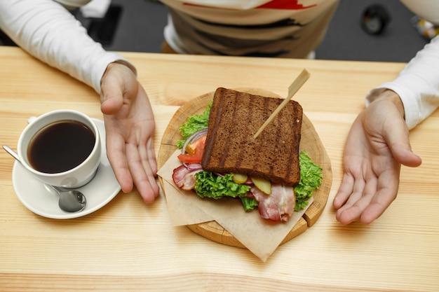 カフェの男は彼の注文サンドイッチとコーヒーを取る Premium写真