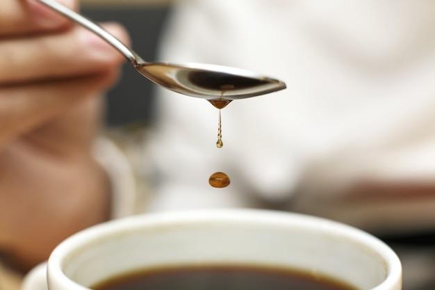コーヒーとマグカップに金属のスプーンから滴り落ちるコーヒーのクローズアップブロブ Premium写真