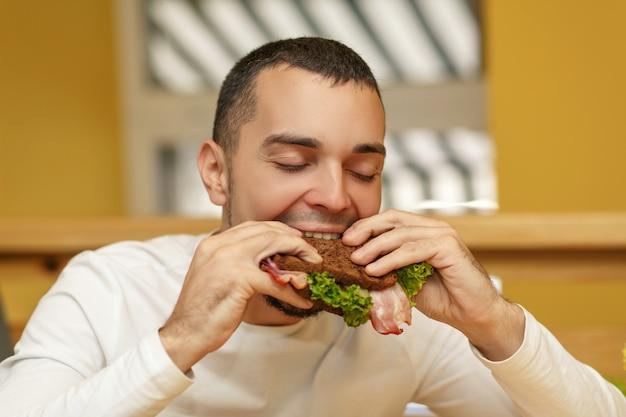 レストランで空腹の若い男がサンドイッチを食べる Premium写真