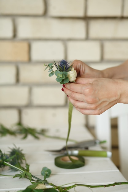 Женщина флористом руки собирает цветы для бутоньерки жениха. событие украшение живыми цветами. флорист рабочий процесс. свадебный банкет Premium Фотографии