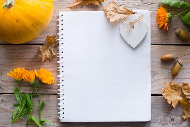 Блокнот на деревянном осеннем столе с тыквой, цветами сухими листьями Premium Фотографии