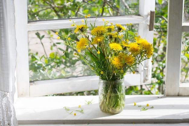 ウィンドウのタンポポの花束 Premium写真