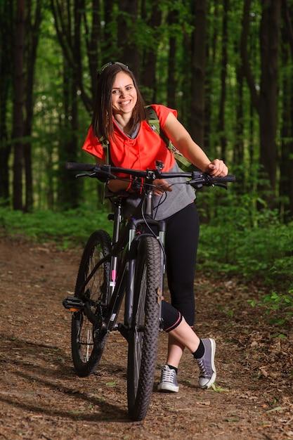 Девушка катается на велосипеде в лесу Premium Фотографии