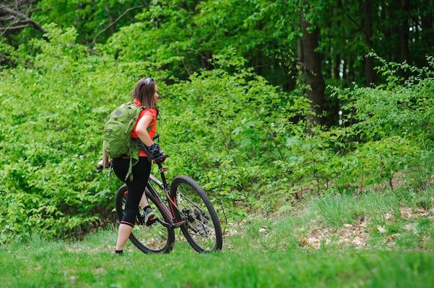 森の中で自転車に乗る女の子 Premium写真