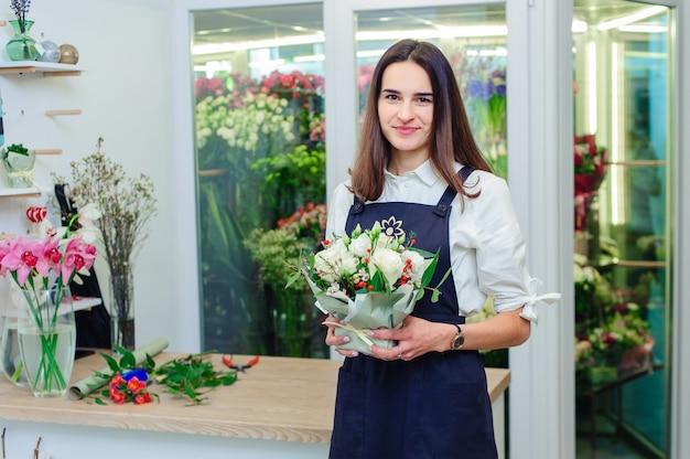 Владелец цветочного магазина делает букет из белых роз Premium Фотографии