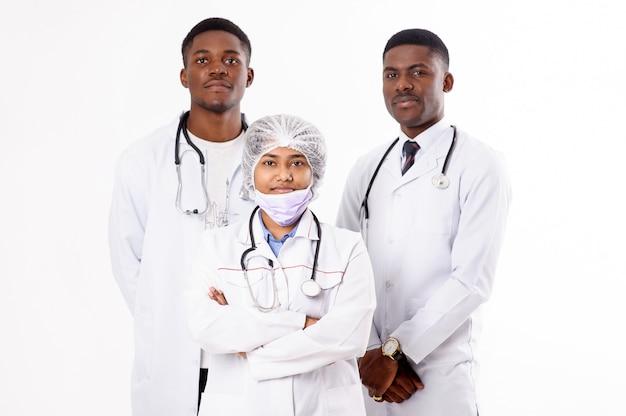 Три доктора на белом. индийская женщина с стетоскоп. африканские мужчины. Premium Фотографии