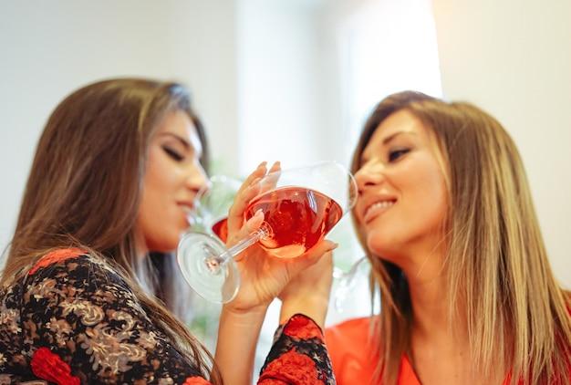 楽しんで家でワインを飲んで幸せな若い女性 Premium写真