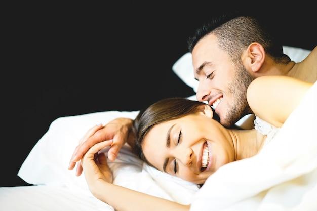 彼らの新婚旅行でベッドに横たわっている恋人たちの若いセクシーなカップル Premium写真