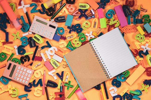 学校概念に戻る。オレンジの背景にノートブックと教育機器。 Premium写真