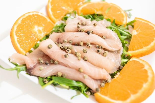 ピーマン、チャイブ、オレンジジュース数滴と新鮮な地中海のメカジキのカルパッチョ Premium写真
