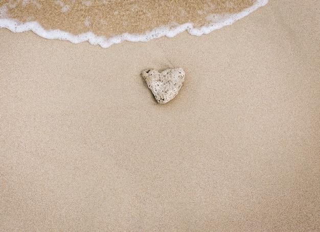 Камень любви в песке Premium Фотографии