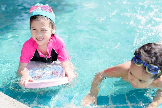 Довольно маленькая девочка плавает в открытом бассейне и веселится со своим другом Premium Фотографии
