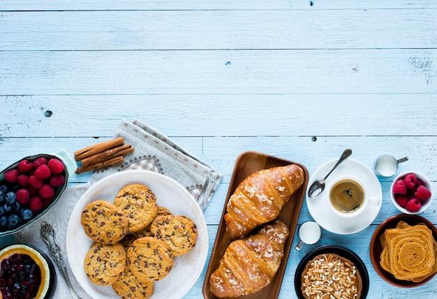 ケーキ、フルーツ、コーヒー、ビスケット、スパイスなどの木のテーブルの上から見る Premium写真