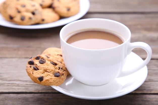 プレートと灰色の背景にコーヒーカップにチョコレートクッキー Premium写真