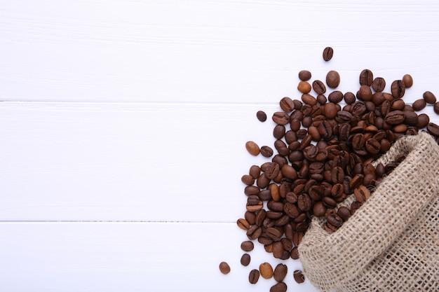 Кофейные зерна в мешочке из ткани на белом столе Premium Фотографии