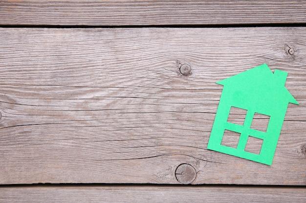 灰色の木製の背景に緑の紙の家 Premium写真