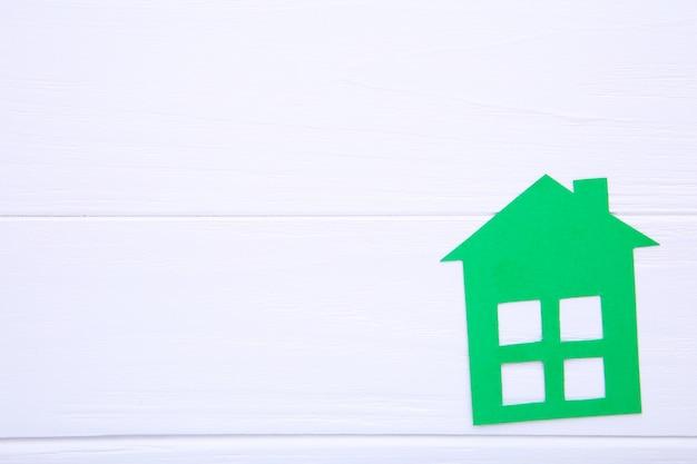 白い背景の上の緑の紙の家 Premium写真