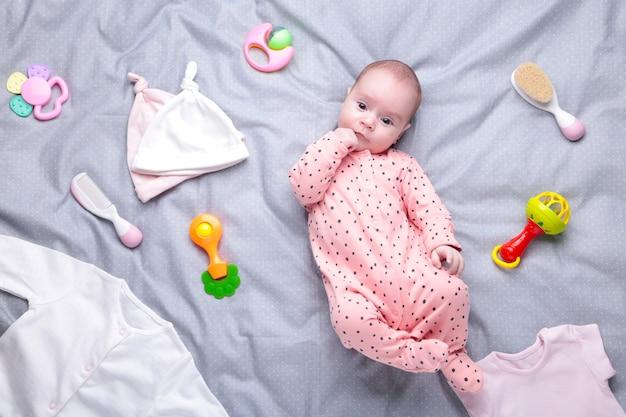 服、トイレタリー、おもちゃ、ヘルスケアアクセサリーを着た白の赤ちゃん。妊娠とベビーシャワーのウィッシュリストまたはショッピングの概要。 Premium写真