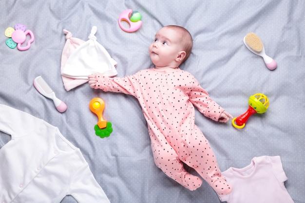 Ребенок на белом с одеждой, туалетными принадлежностями, игрушками и медицинскими принадлежностями. список пожеланий или обзор покупок для беременности и детского душа. Premium Фотографии