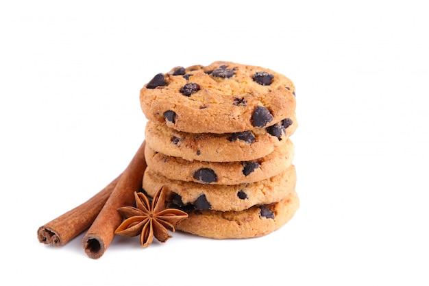 シナモンスティックと白い背景で隔離のスターアニスとチョコレートクッキー。 Premium写真