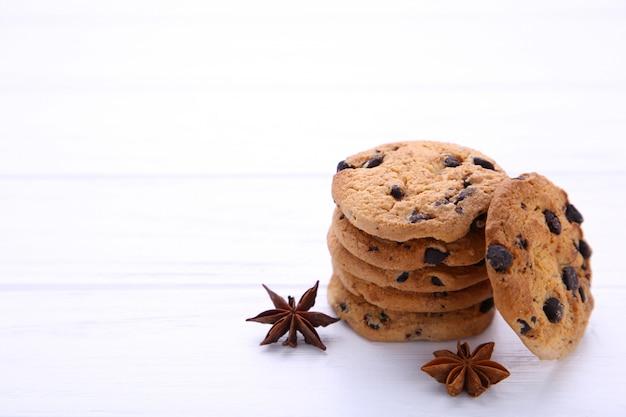シナモンスティックと白い背景の上のスターアニスとチョコレートクッキー。 Premium写真