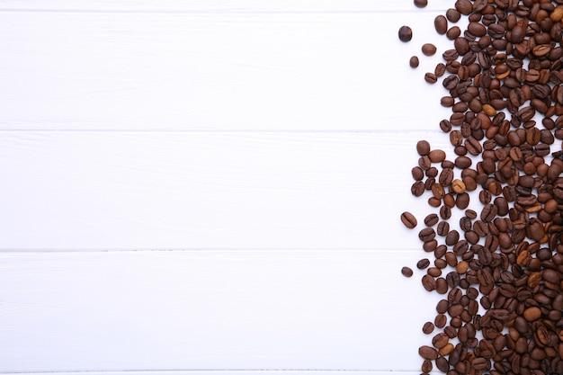 白い木製の背景に天然のコーヒー豆 Premium写真