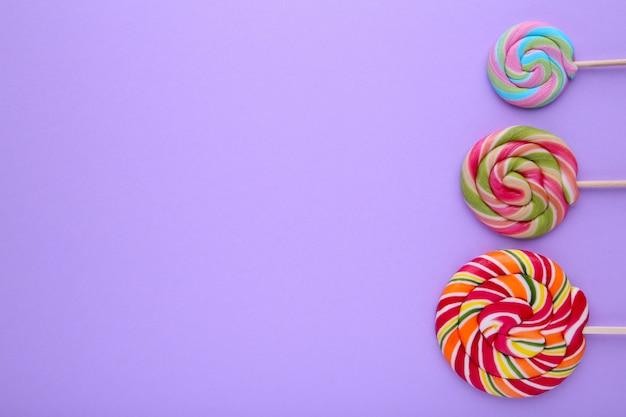 紫色の背景、お菓子に多くのカラフルなロリポップ Premium写真