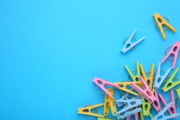 青色の背景にプラスチック製の服のピン Premium写真