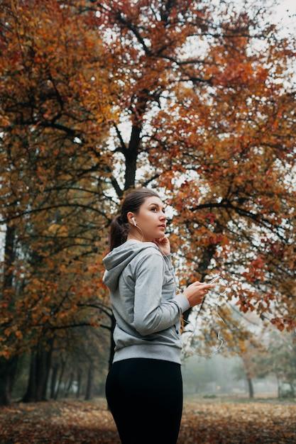 Женщина включает музыку для бега в лесу Premium Фотографии