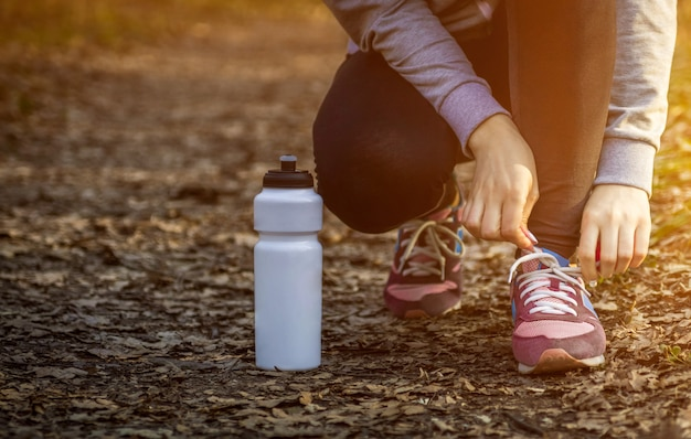 Женщина завязывает шнурки. Premium Фотографии