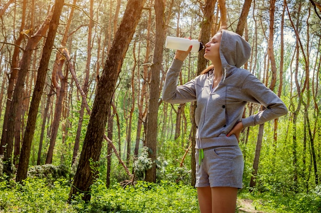 Женщина пьет воду после бега в лесу Premium Фотографии