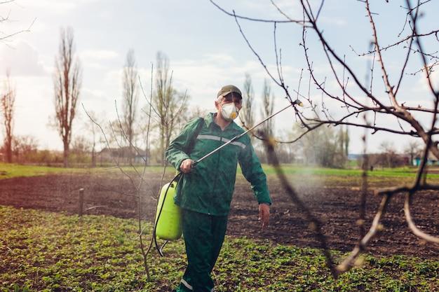 秋の庭の昆虫に対して手動農薬噴霧器で木を噴霧する農家。農業および園芸 Premium写真