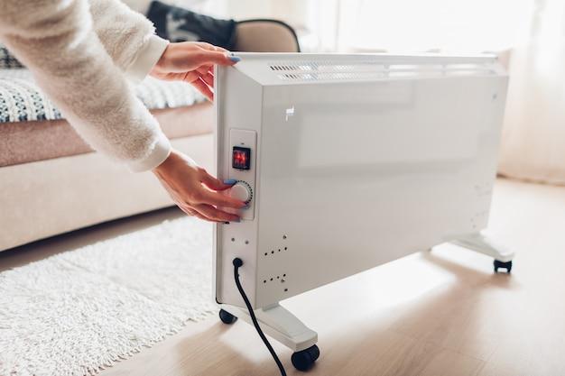 冬に家でヒーターを使用します。ヒーターの温度を調整する女性。暖房シーズン。 Premium写真