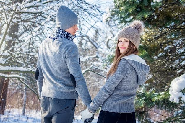 愛の若いカップルが森の中を歩く Premium写真